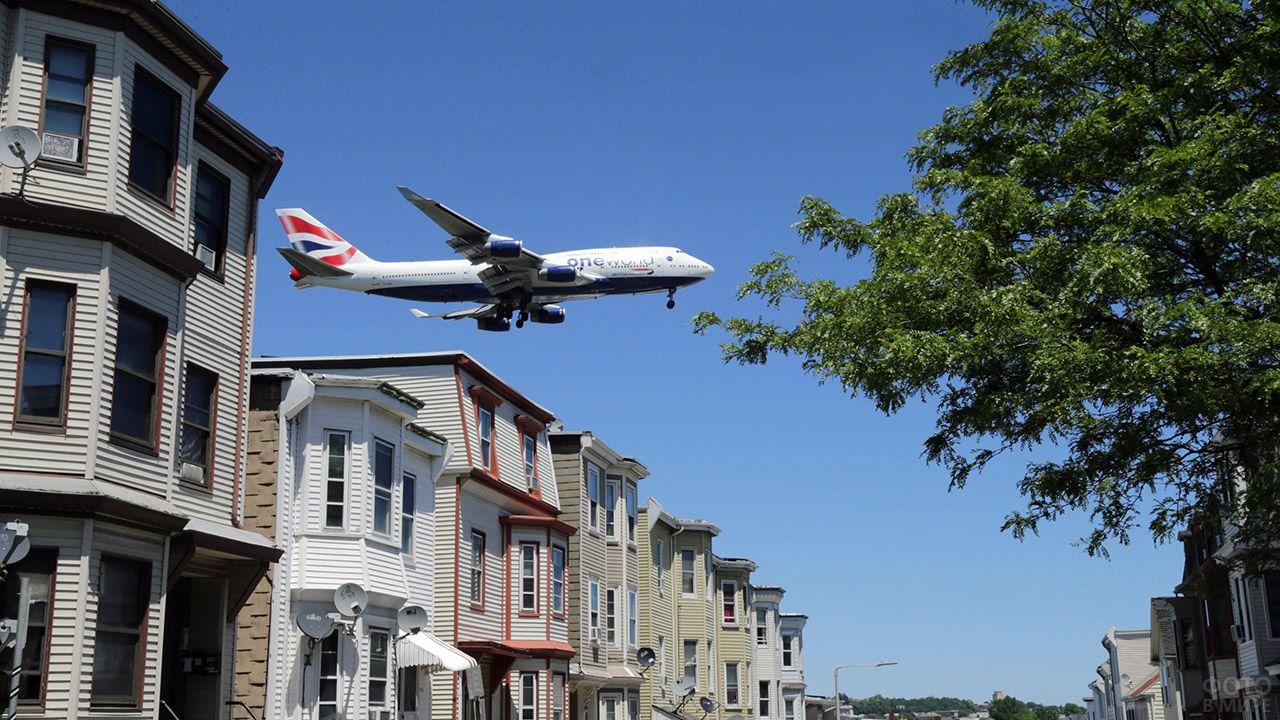 Низколетящий самолёт над крышами домов