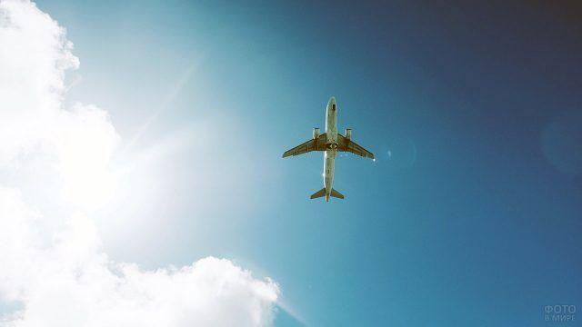 Парящий в зените солнца пассажирский самолёт