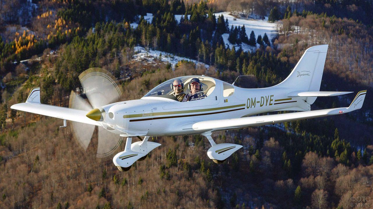 Пилоты спортивного самолёта смотрят в камеру, пролетая над лесом