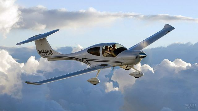Полёт спортивного самолёта среди облаков