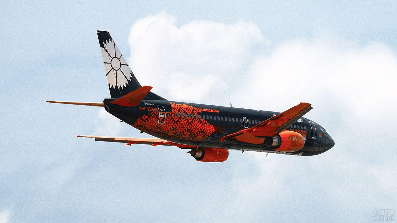Самолёт гражданской авиации в красно-чёрной ливрее с белой гвоздикой