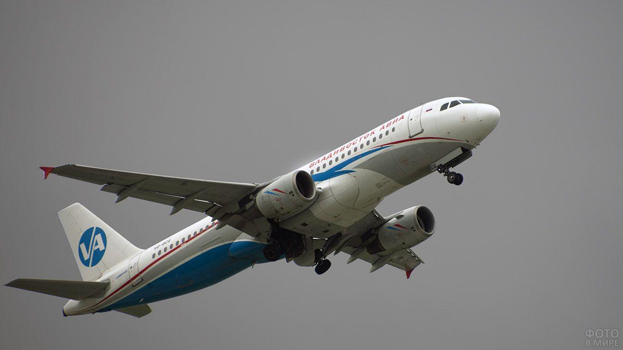 Самолёт владивостокской авиакомпании на фоне серого неба