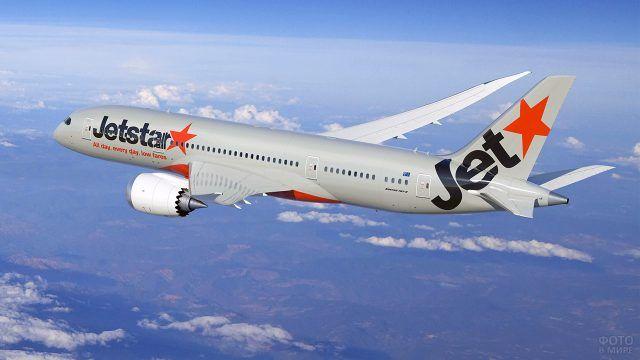 Серая ливрея с красными звёздами летящего самолёта компании Jetstar
