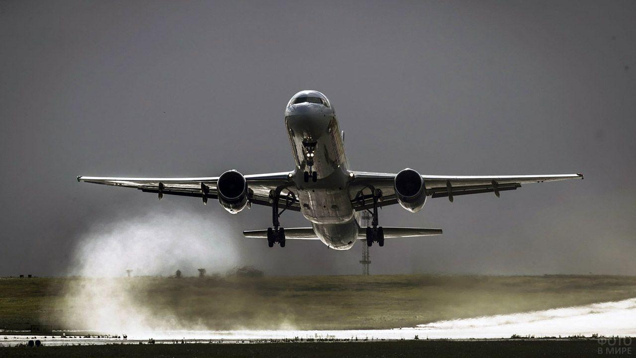 Серебристый Боинг над взлётно-посадочной полосой
