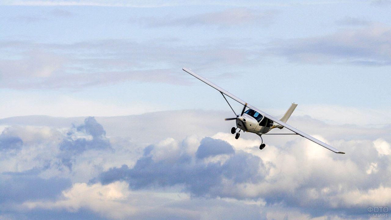 Спортивный самолёт над облаками