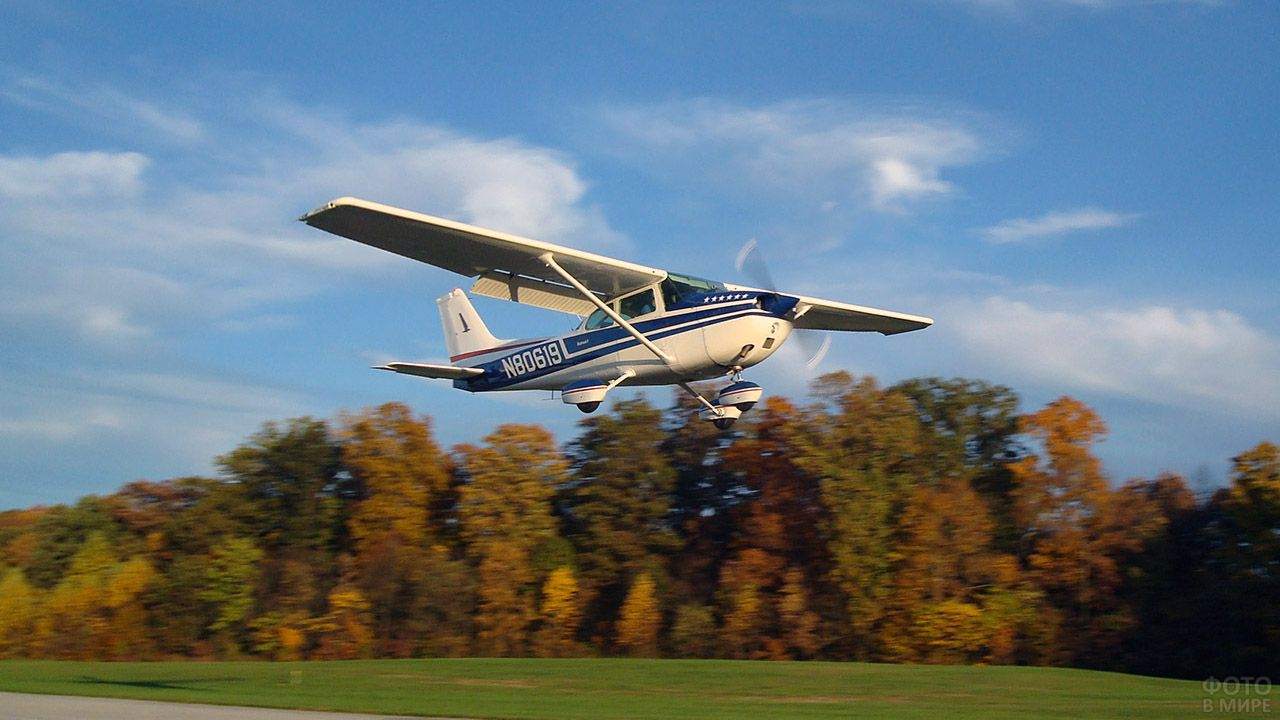 Спортивный самолёт взлетает над деревьями