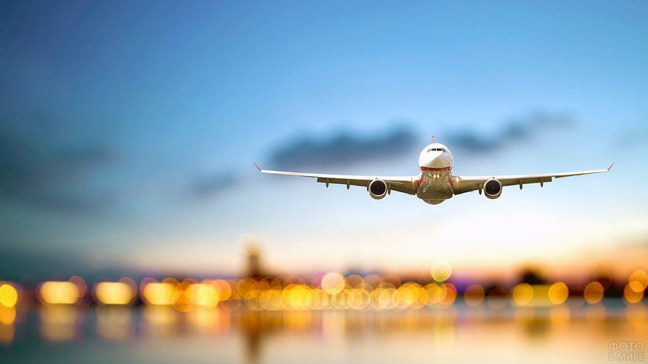 Взлетающий самолёт на фоне вечерних огней города