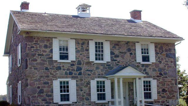 Черепичная двускатная крыша каменного двухэтажного особняка
