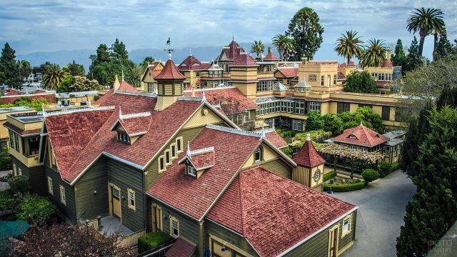 Комбинированная черепичная крыша зелёного особняка в тропиках