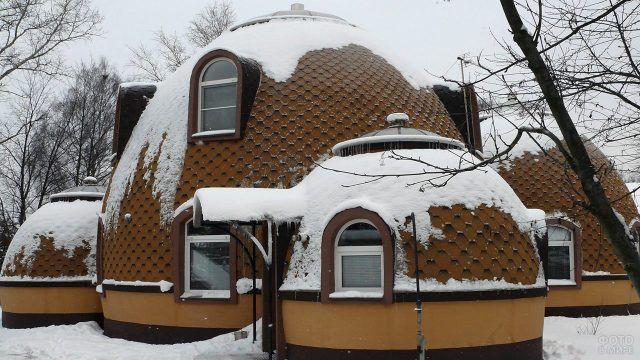 Куполообразная крыша оригинального загородного дома занесённого снегом