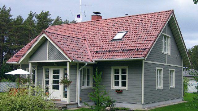 Многощипцовая черепиная крыша садового дома с серым сайдингом