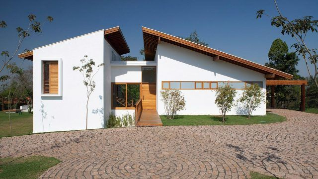 Необычная крыша белого загородного дома