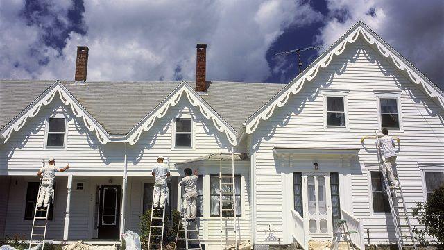 Покраска фасада деревянного загородного дома с вальмовой крышей и прерванным фронтоном