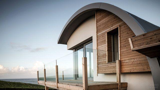 Современный загородный дом у побережья моря с округлой крышей-волной