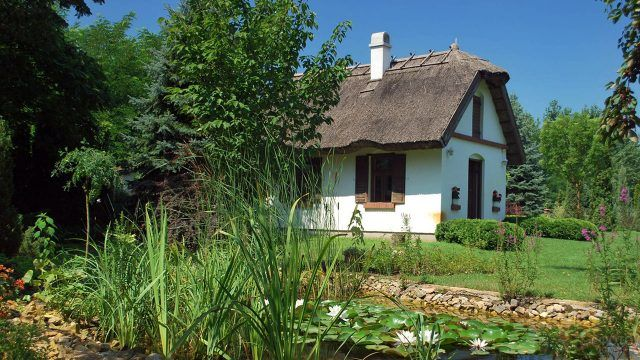 Белая дача с полувальмовой соломенной крышей в зелёном саду с прудом