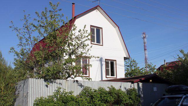 Белый дачный дом с мансардой с деревом под окнами