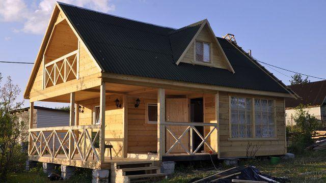 Брусовой дачный дом с широким крыльцом