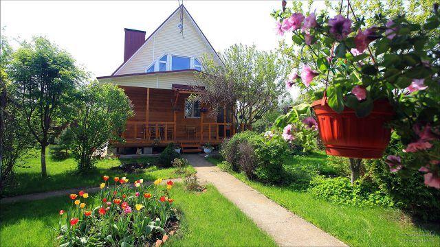Цветущий участок перед деревянным дачным домом с мансардой и широким крыльцом