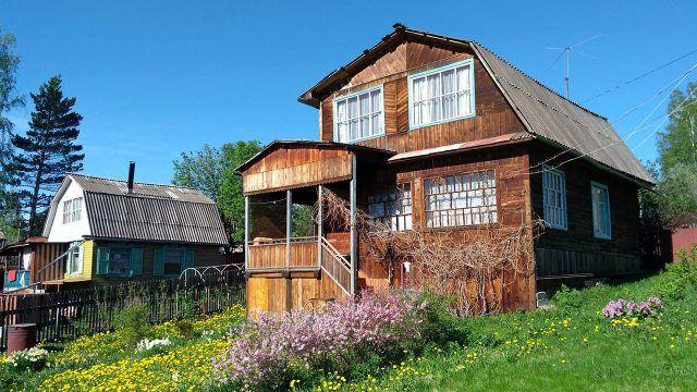 Деревянная двухэтажная дача на цветущем склоне холма