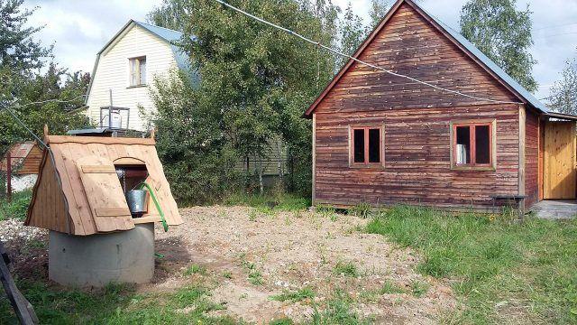 Колодец на участке перед садовым деревянным домом