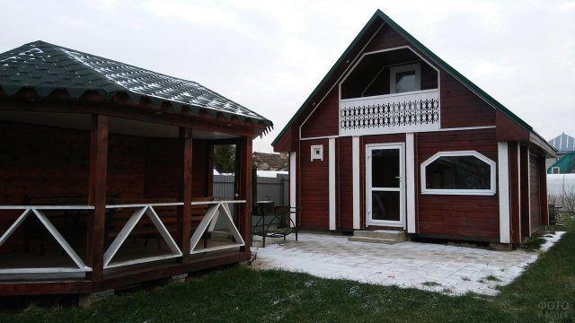 Коричневый с белыми вставками деревянный домик и беседка во дворе