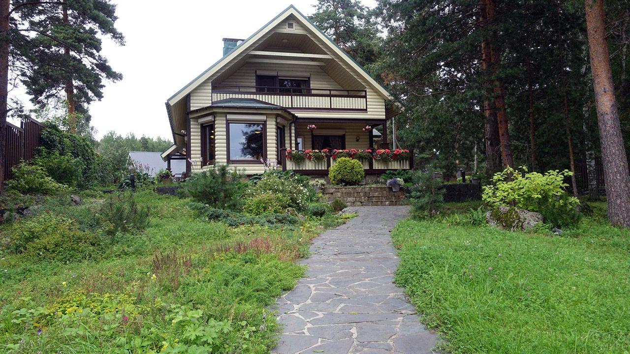 Красивый бревенчатый садовый дом с балконом эркером и цветами на веранде