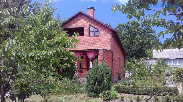Красивый кирпичный дом на зелёном садовом участке
