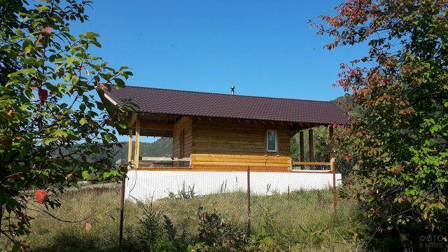 Современный дачный домик с открытой верандой в саду с плодовыми деревьями
