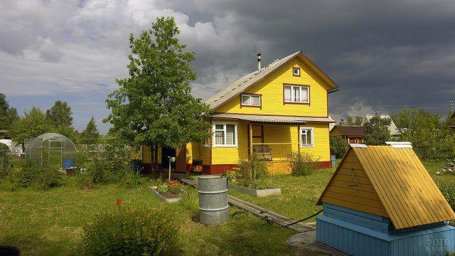 Жёлтый дачный дом с ассимитричной крышей