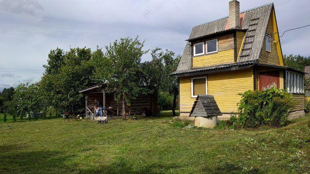 Жёлтый садовый домик с высокой двускатной крышей и застеклённой верандой