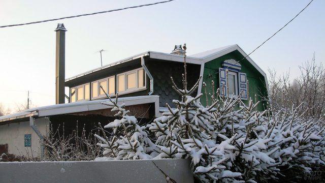 Зимние ели у фасада двухэтажной дачи
