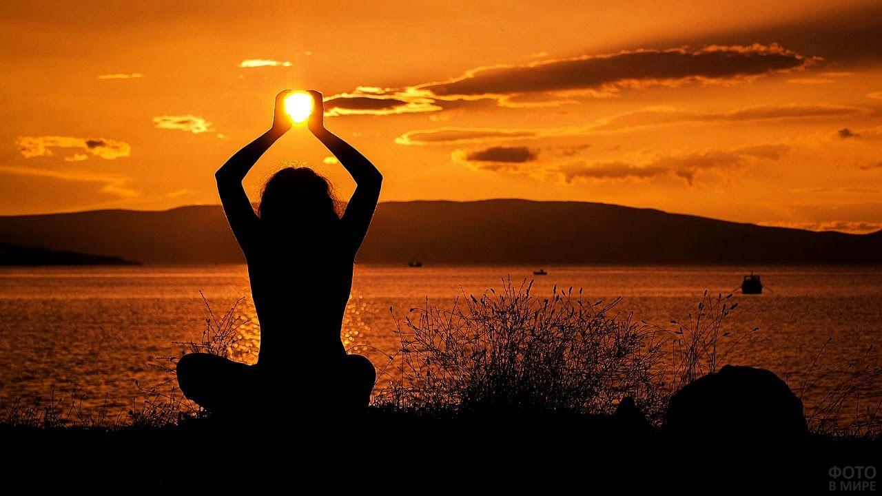 Девушка держит в руках заходящее солнце