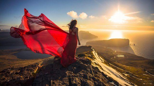 Девушка в алом платье на верхушке горы на фоне заката