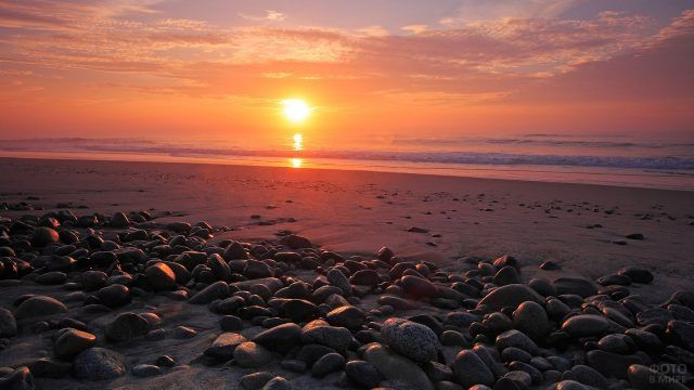 Камни на пляже и море в лучах заката