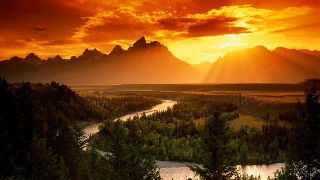 Река и горные силуэты в лучах заходящего солнца