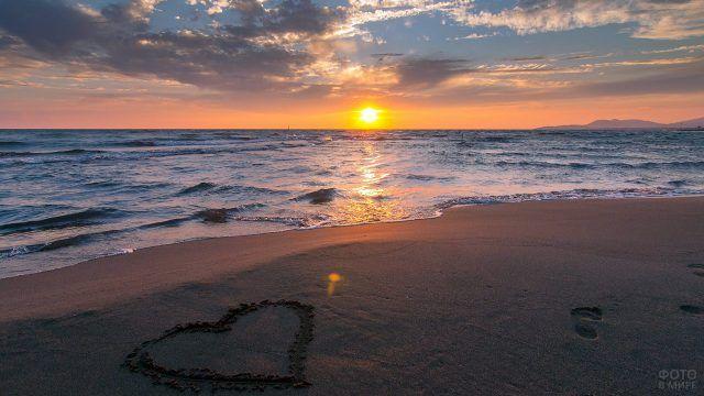 Сердце нарисованное на песке пляжа у моря в закатных лучах солнца