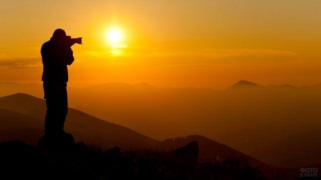 Силуэт фотографа на фоне заката в горах