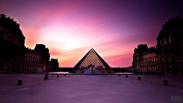 Стеклянная пирамида в Лувре на фоне пурпурного закатного неба