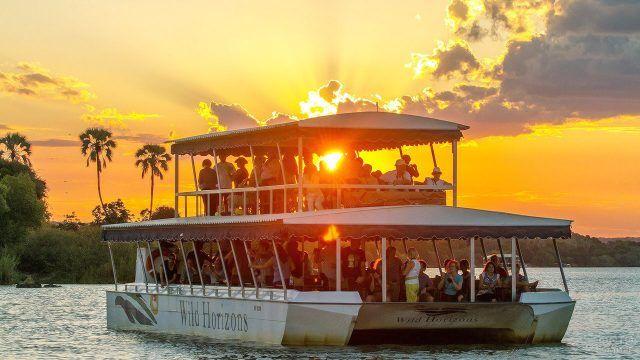 Туристический круизный корабль на фоне заката над рекой Замбези