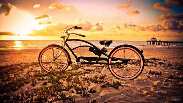 Велосипед на пляже на фоне заката над морем