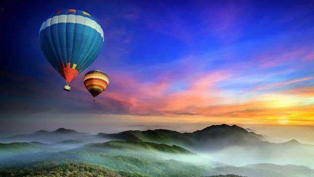 Воздушные шары летят над горами на фоне заката