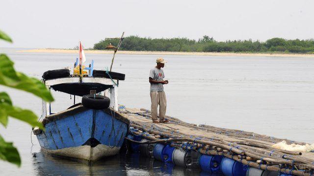 Абориген с ветхой лодкой на импровизированном пирсе Менджангана