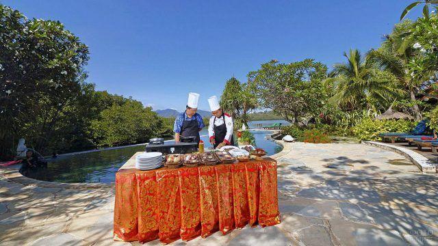 Два повара у стола с национальной едой на пляже при отеле