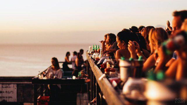 Людное кафе в лучах заката над пляжем Бали