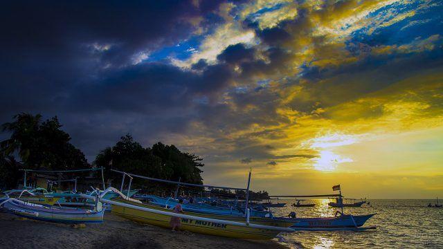 Лодки на песке вечернего пляжа на Бали