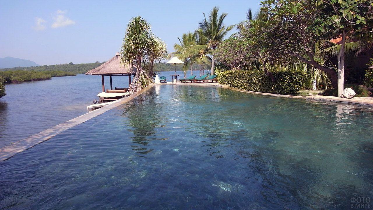 Пальмы и бунгало на пляже Менджангана на Бали