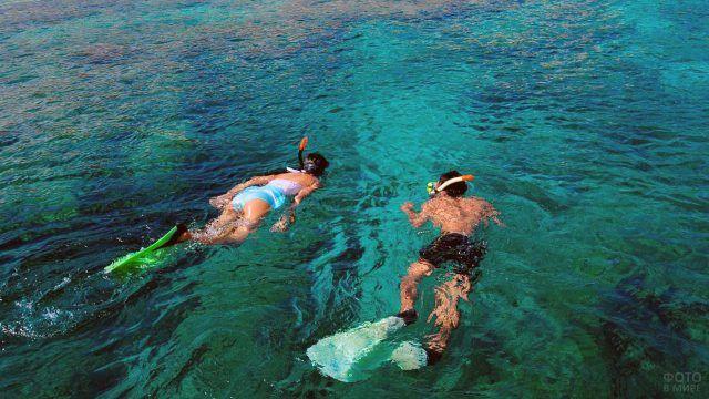 Пара дайверов на мелководье у пляжа Менджангана на Бали