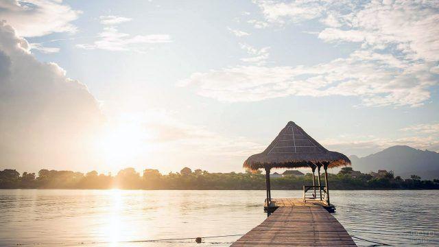 Рассвет над пирсом в национальном стиле на острове Менджанган на Бали