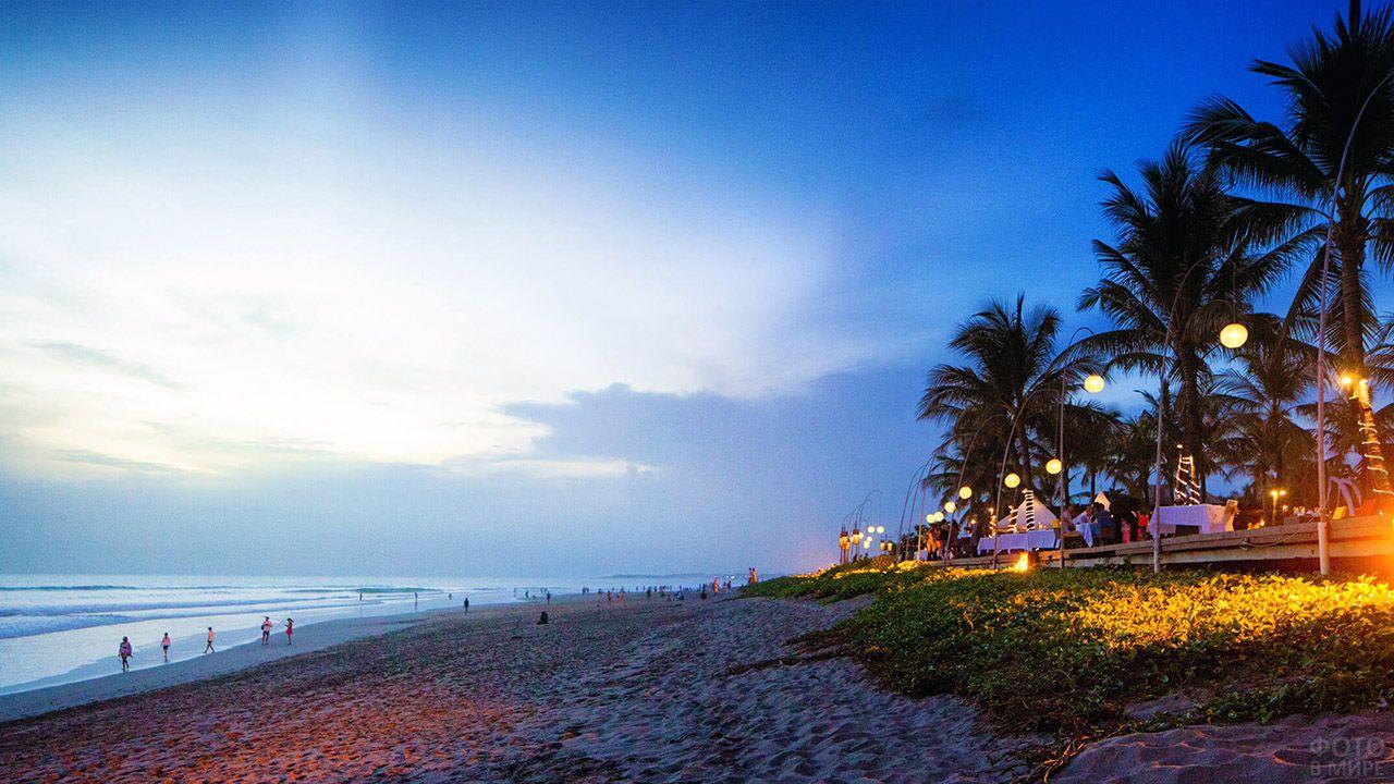 Ресторан под пальмами на вечернем пляже Денпасара