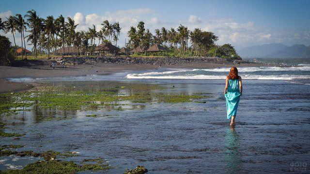 Рыжеволосая девушка в голубом платье на мелководье пляжа Бали